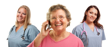 Senior Woman Using Cell Phone and Female Doctors. Happy Senior Woman Using Cell Phone with Female Doctors or Nurses Behind Isolated on a White Background Royalty Free Stock Photography