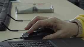Senior woman using computer mouse. Wrinkled hand push buttons on mouse and move it on the table. Close-up stock footage