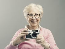Senior woman using a digital camera. Cheerful happy senior woman using a digital camera, she is smiling stock images