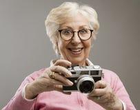 Senior woman using a digital camera. Cheerful happy senior woman using a digital camera, she is smiling royalty free stock photo