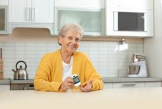 Senior woman using digital glucometer. Diabetes control stock photography