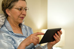 Senior woman using digital tablet in bed Stock Photo