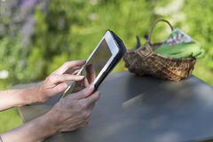 Senior woman using a digital tablet computer in her garden Royalty Free Stock Image