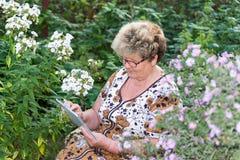 Senior woman using digital tablet in home garden Stock Photography