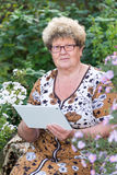 Senior woman using digital tablet in home garden Royalty Free Stock Photo