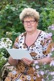 Senior woman using digital tablet in home garden Royalty Free Stock Photo