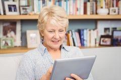 Senior woman using digital tablet at home Royalty Free Stock Image
