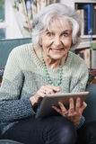 Senior Woman Using Digital Tablet At Home Royalty Free Stock Photos