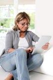 Senior woman using digital tablet at home Royalty Free Stock Photo