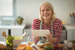 Senior woman using digital tablet. In kitchen Royalty Free Stock Photos