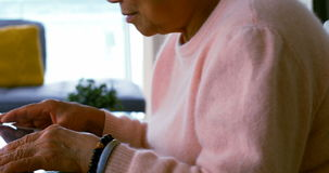 Senior woman using digital tablet in living room stock video