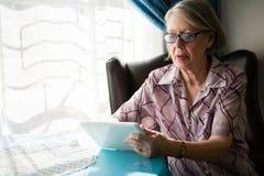 Senior woman using digital tablet while sitting in nursing home Stock Photo