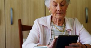 Senior woman using digital tablet at table 4k stock footage