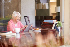 Senior Woman Using Digital Tablet Through Window Royalty Free Stock Image