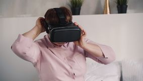Senior woman is using digital technology of augmented virtual reality glasses. Elderly female is watching and gaming in 3d mode 360 screen. Excited futuristic stock video footage