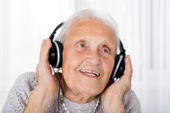 Senior Woman Using Headphone At Home Royalty Free Stock Images