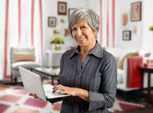 Senior woman using her handheld laptop Stock Images