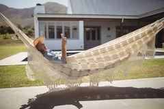 Senior woman using her mobile phone while relaxing in hammock Stock Image