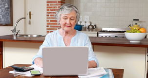 Senior woman using laptop and calculator. At home stock video
