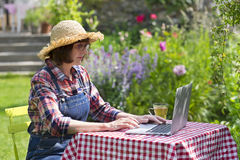 Senior woman using a laptop computer in her garden Stock Image