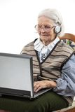 Senior woman using laptop computer over white Stock Photos