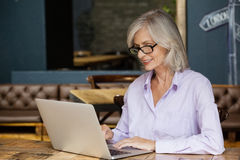 Senior woman using laptop computer while sitting at table. In cafe shop Royalty Free Stock Images