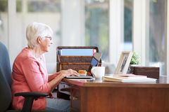 Senior Woman Using Laptop On Desk At Home. Sitting Down Stock Photos