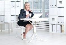 Senior woman  using laptop and drinking tea Stock Photo
