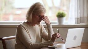 Senior woman using laptop feeling discomfort taking off glasses