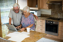 Senior woman using laptop in the kitchen. At home Royalty Free Stock Photo