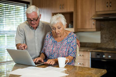 Senior woman using laptop in the kitchen. At home Royalty Free Stock Photography