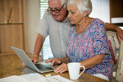 Senior woman using laptop in the kitchen. At home Royalty Free Stock Images