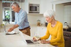 Senior woman using laptop in kitchen. Senior women using laptop in kitchen while men cleaning dishes in background Stock Images