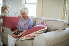 Senior woman using laptop in living room Royalty Free Stock Image