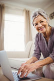 Senior woman using laptop in living room Stock Image
