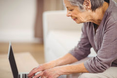 Senior woman using laptop in living room Royalty Free Stock Photo