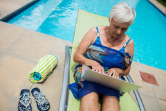 Senior woman using laptop on lounge chair Stock Image