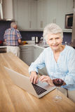 Senior woman using laptop and man working in kitchen Royalty Free Stock Image