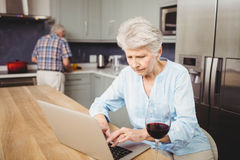 Senior woman using laptop and man working in kitchen Royalty Free Stock Photo