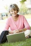 Senior woman using laptop outdoors Stock Photography