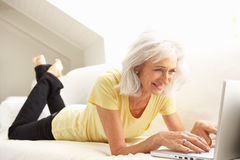 Senior Woman Using Laptop Relaxing Sitting On Sofa. At Home Royalty Free Stock Photo