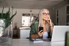 Senior woman using laptop and smartphone. Happy senior woman holding smartphone and laptop daydreaming while looking away. Successful stylish old woman working royalty free stock photos