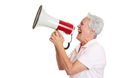 Senior woman using a megaphone. Senior woman screaming loudly in a megaphone Stock Photo