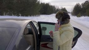 Senior woman using mobile phone for calling standing nearly car on winter road. In snowy forest. Old woman calling by smartphone in winter forest stock video footage