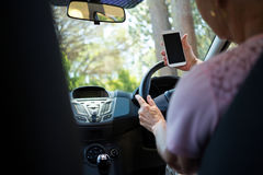 Senior woman using mobile phone while driving a car Stock Image