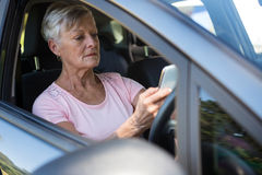 Senior woman using mobile phone while driving car Royalty Free Stock Photos