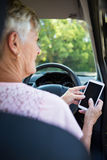 Senior woman using mobile phone while driving a car Royalty Free Stock Photos