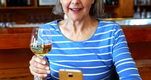 Senior woman using mobile phone while having wine 4k. Senior woman using mobile phone while having wine in bar 4k stock video