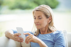 Senior woman using mobile phone in living room royalty free stock photo