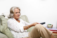 Senior woman using remote control while relaxing on armchair at home Royalty Free Stock Images
